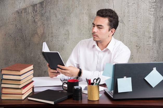 Jonge zakenman die notities leest bij het bureau.