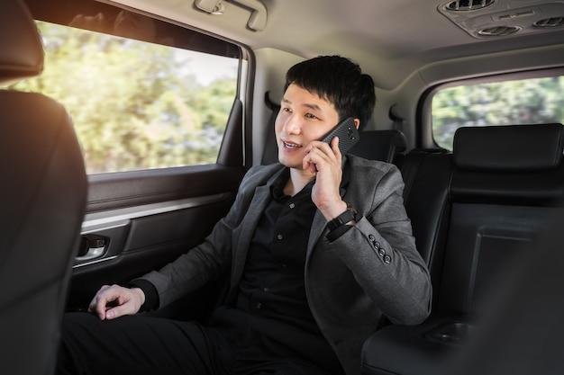 Jonge zakenman die op de mobiele telefoon praat terwijl hij op de achterbank van de auto zit