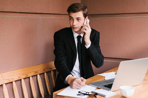 Jonge zakenman die op de telefoon in het bureau spreekt