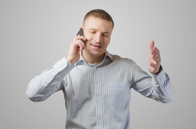 Jonge zakenman die op een celtelefoon spreekt. geïsoleerd op wit oppervlak