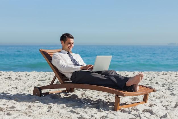 Jonge zakenman die op een ligstoel met zijn laptop ligt