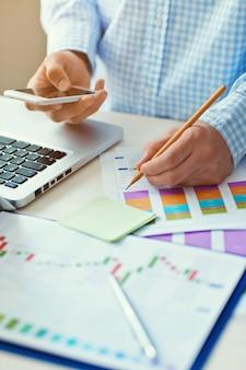 Jonge zakenman die op kantoor werkt. notitieboekje op houten tafel, papieren, documenten, statistieken