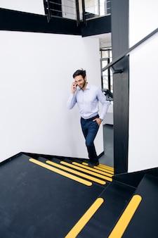 Jonge zakenman die op mobiele telefoon spreekt en op de treden in bureau beklimt