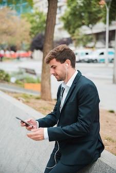 Jonge zakenman die op straat leunt die mobiele telefoon met oortelefoon op zijn oren met behulp van