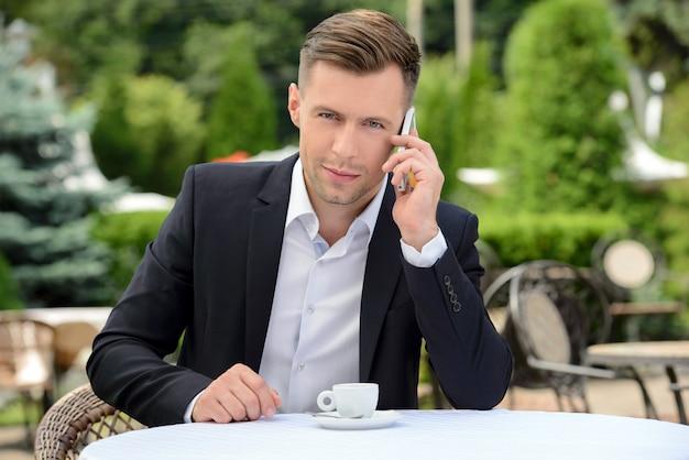 Jonge zakenman die op telefoon spreekt.