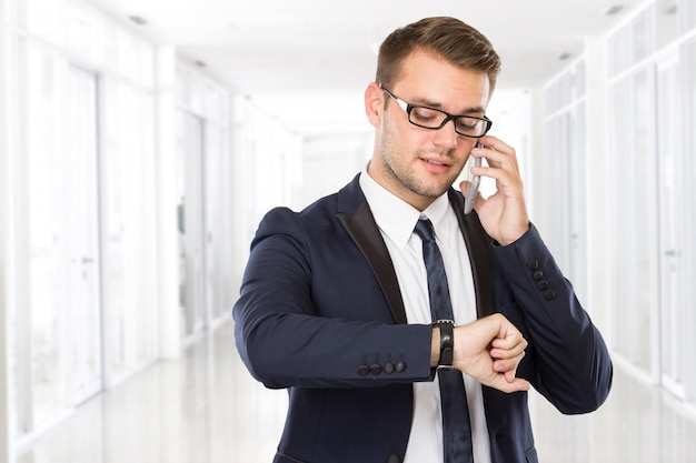 Jonge zakenman die op zijn gsm spreekt terwijl het bekijken zijn horloges