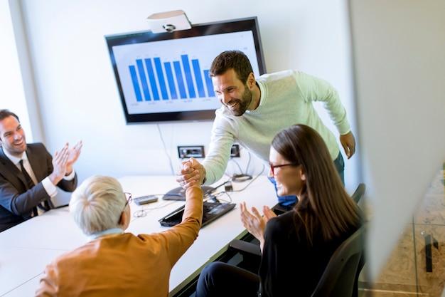 Jonge zakenman die projectstrategie voorstelt die ideeën op interactieve whiteboard in bureau toont