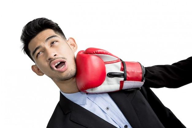 Jonge zakenman die stempel in zijn gezicht met rode bokshandschoenen krijgt. concurrentie bedrijfsconcept