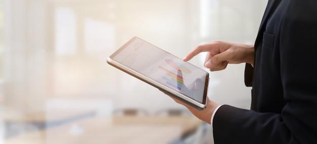 Jonge zakenman die tablet in bureau gebruikt