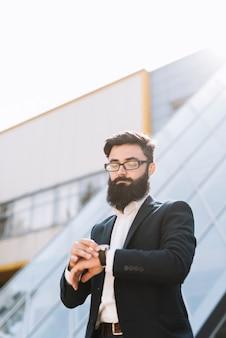 Jonge zakenman die tijd controleert die zich tegen de bureaubouw bevindt
