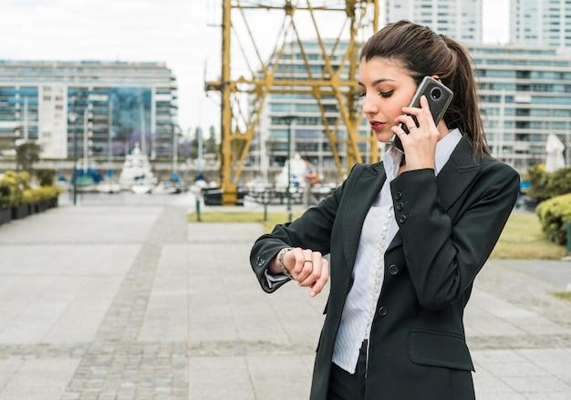 Jonge zakenman die tijd controleert op polshorloge terwijl het spreken op mobiele telefoon