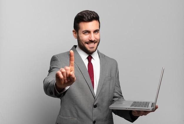 Jonge zakenman die trots en zelfverzekerd glimlacht en nummer één triomfantelijk laat poseren, zich een leider voelt en een laptop vasthoudt