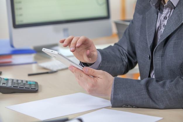 Jonge zakenman die vanuit zijn kantoor op zijn tablet werkt