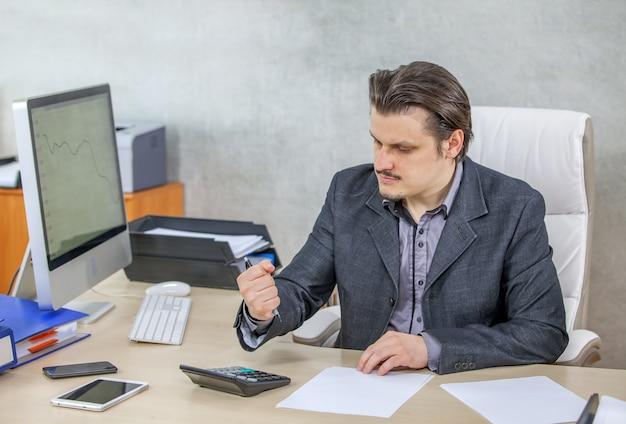 Jonge zakenman die vanuit zijn kantoor werkt - het concept van hard werken