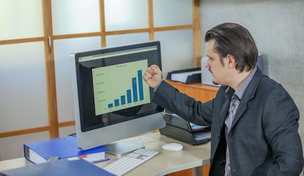 Jonge zakenman die vanuit zijn kantoor werkt - het concept van succes