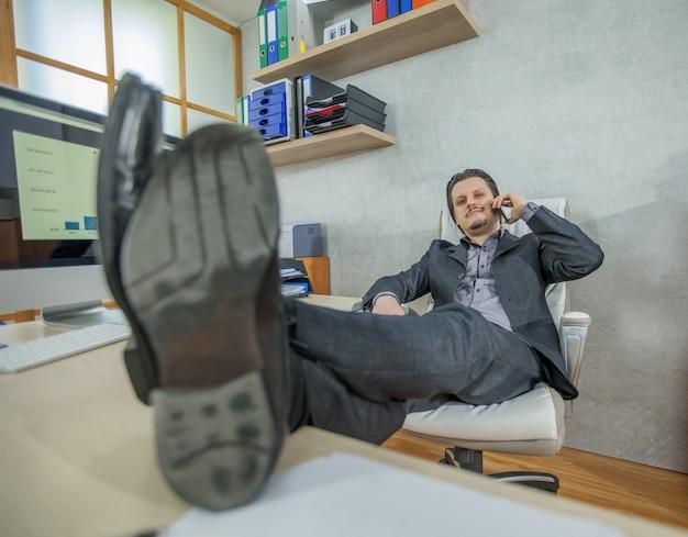 Jonge zakenman die vanuit zijn kantoor werkt tijdens het gesprek aan de telefoon en ontspant