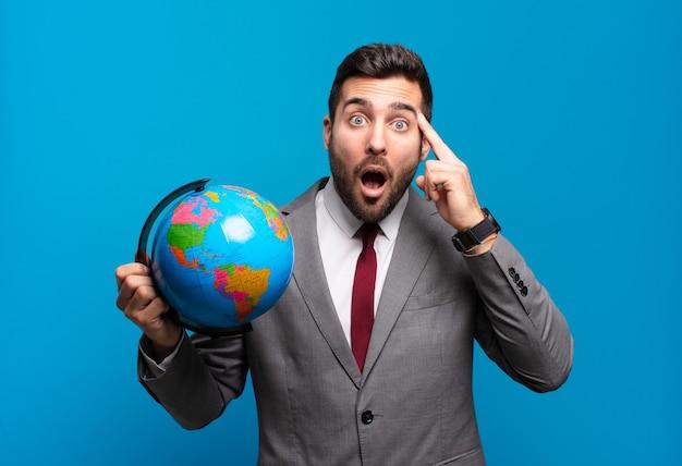 Jonge zakenman die verbaasd, met open mond, geschokt kijkt, een nieuwe gedachte, idee of concept realiseert dat een wereldbolkaart vasthoudt