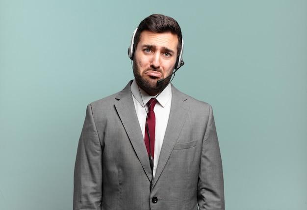 Jonge zakenman die verdrietig en zeurderig is met een ongelukkige blik, huilend met een negatief en gefrustreerd houding telemarketingconcept
