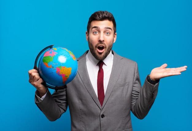 Jonge zakenman die verrast en geschokt kijkt en een wereldbol vasthoudt