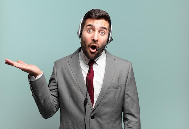 Jonge zakenman die verrast en geschokt kijkt, met open mond terwijl hij een object vasthoudt met een open hand aan de zijkant telemarketingconcept