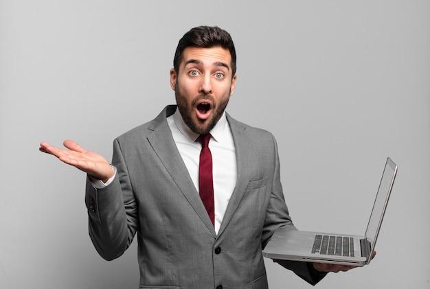 Jonge zakenman die verrast en geschokt kijkt