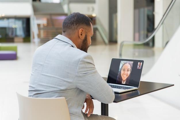 Jonge zakenman die via laptop babbelt