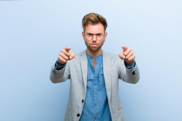 Jonge zakenman die vooruit op camera met zowel vingers als boze uitdrukking richt, die u vertelt om uw plicht tegen blauw te doen
