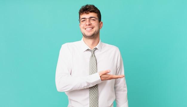 Jonge zakenman die vrolijk lacht, zich gelukkig voelt en een concept in kopieerruimte toont met de palm van de hand