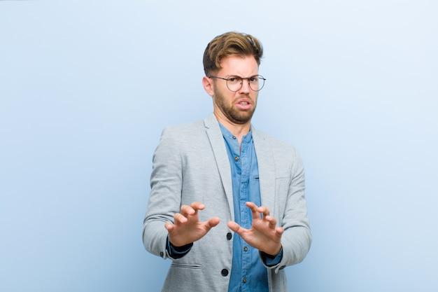 Jonge zakenman die walgt en misselijk voelt, achteruitgaand van iets smerig, stinkend of stinkend, zeggend tegen blauw