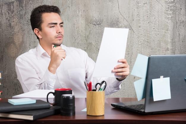 Jonge zakenman die werkdocumenten bij het bureau kijkt.