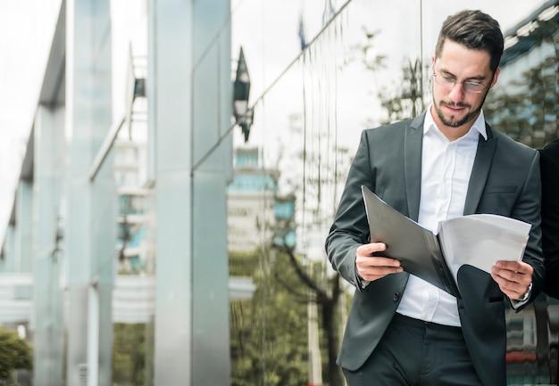 Jonge zakenman die zich bij in openlucht bevindt die het document leest