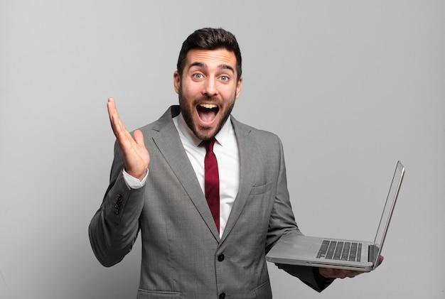 Jonge zakenman die zich blij, opgewonden, verrast of geschokt voelt, glimlacht en verbaasd is over iets ongelooflijks en een laptop vasthoudt