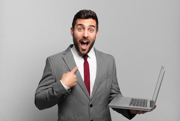 Jonge zakenman die zich blij, verrast en trots voelt, naar zichzelf wijst met een opgewonden, verbaasde blik en een laptop vasthoudt