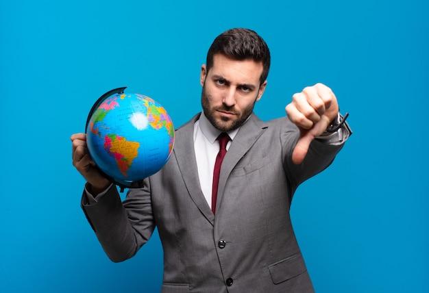 Jonge zakenman die zich boos, boos, geïrriteerd, teleurgesteld of ontevreden voelt, duimen naar beneden laat zien met een serieuze blik die een wereldbolkaart vasthoudt