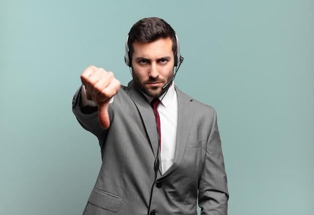 Jonge zakenman die zich boos, boos, geïrriteerd, teleurgesteld of ontevreden voelt, duimen naar beneden toont met een serieuze blik op telemarketingconcept