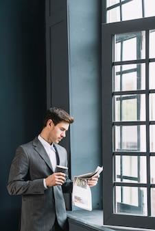 Jonge zakenman die zich dichtbij de kop van de vensterholding van de krant van de koffielezing bevindt