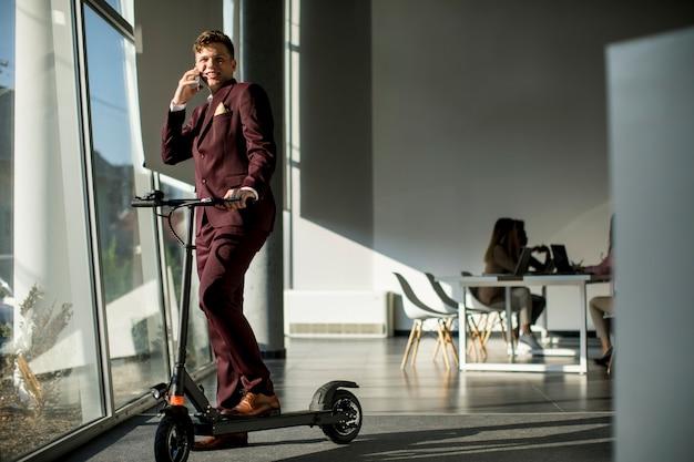Jonge zakenman die zich door het bureauvenster met elektrische autoped bevindt en mobiele telefoon met behulp van