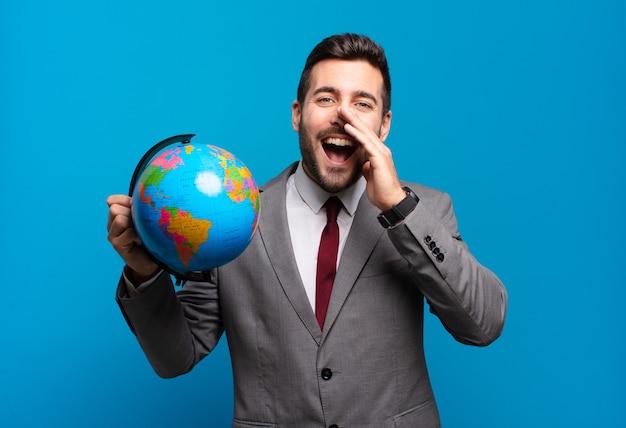 Jonge zakenman die zich gelukkig, opgewonden en positief voelt, een grote schreeuw geeft met de handen naast de mond, roept terwijl hij een wereldbolkaart vasthoudt