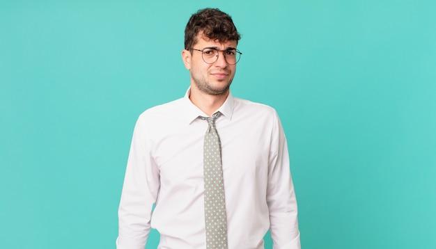 Jonge zakenman die zich verdrietig, overstuur of boos voelt en opzij kijkt met een negatieve houding, fronsend in onenigheid