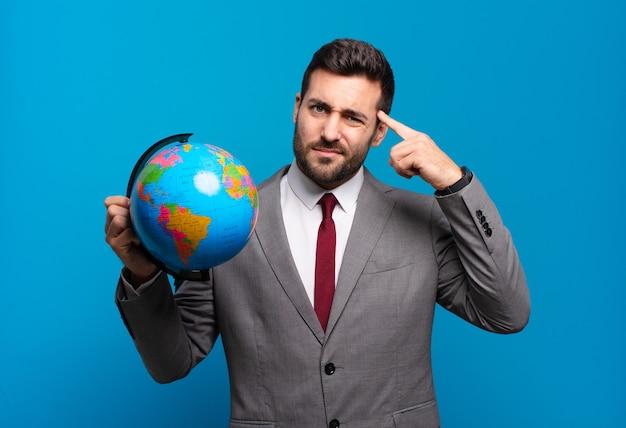Jonge zakenman die zich verward en verbaasd voelt en laat zien dat je gek, gek of gek bent met een wereldbolkaart