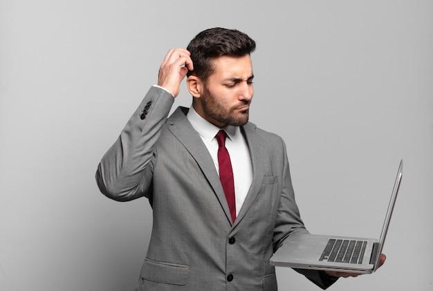Jonge zakenman die zich verward en verward voelt, hoofd krabt en opzij kijkt en een laptop vasthoudt