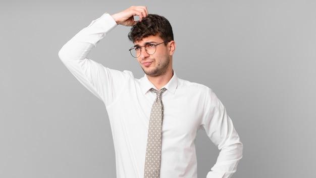 Jonge zakenman die zich verward en verward voelt, hoofd krabt en opzij kijkt