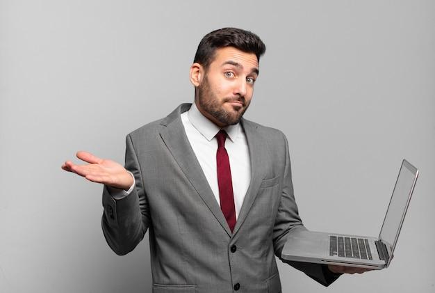 Jonge zakenman die zich verward en verward voelt, twijfelt, weegt of verschillende opties kiest met grappige uitdrukking en een laptop vasthoudt
