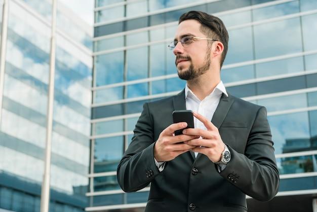 Jonge zakenman die zich voor de bureaubouw bevindt die mobiele telefoon houdt