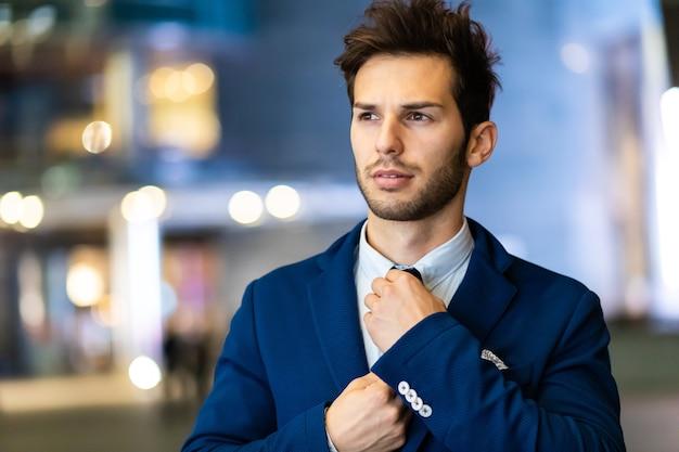 Jonge zakenman die zijn blik in de avond buiten aanpast