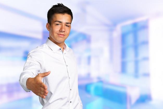 Jonge zakenman die zijn hand uitdeelt