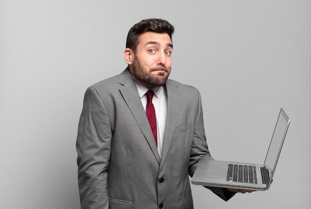 Jonge zakenman die zijn schouders ophaalt, zich verward en onzeker voelt, twijfelt met gekruiste en verbaasde armen kijkt en een laptop vasthoudt