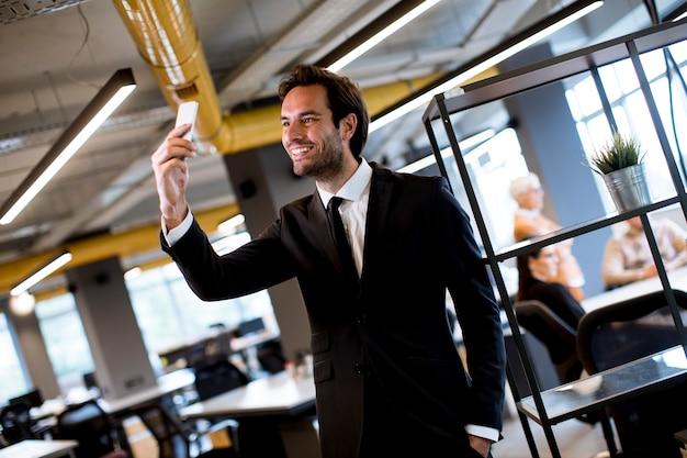 Jonge zakenman die zwart kostuum dragen die moderne smartphone in het bureau gebruiken