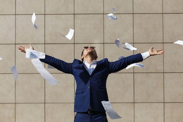 Jonge zakenman door weg papieren die zich op de straat bevinden