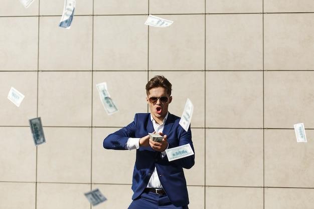 Jonge zakenman doorloopt rond dollars en danst op straat